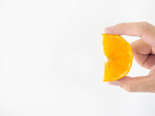 A Man's Hand Holds An Orange T...