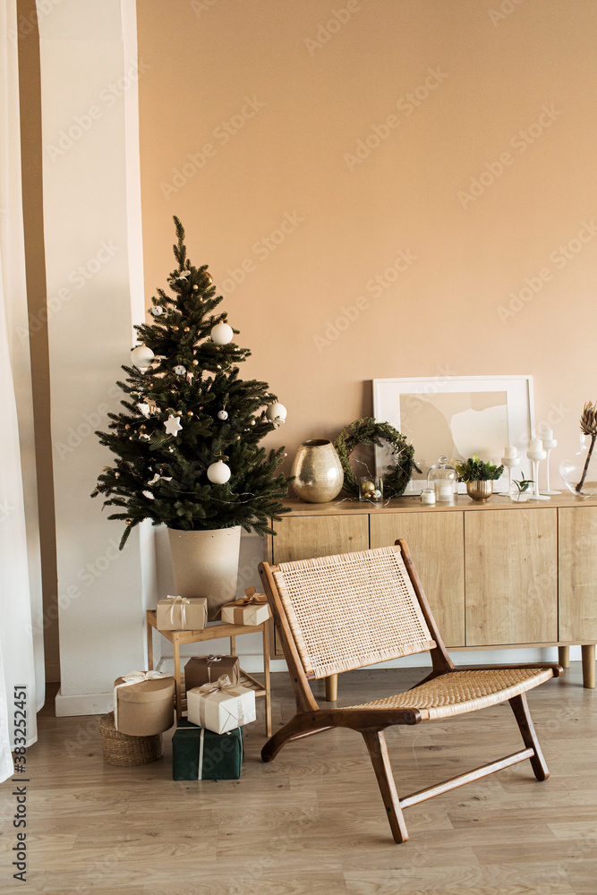 Fototapeta Modern home interior design concept. Comfortable cozy living room decorated with Christmas tree with gifts, rattan chair. Christmas / New Year celebration decorations.
