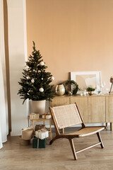 Modern home interior design concept. Comfortable cozy living room decorated with Christmas tree with gifts, rattan chair. Christmas / New Year celebration decorations.