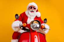 Portrait Of His He Nice Funny Cheerful Cheery Cool Hipster Santa Riding Moped Fast Speed Travel Road Way Trip Having Fun Leisure Isolated Bright Vivid Shine Vibrant Yellow Color Background