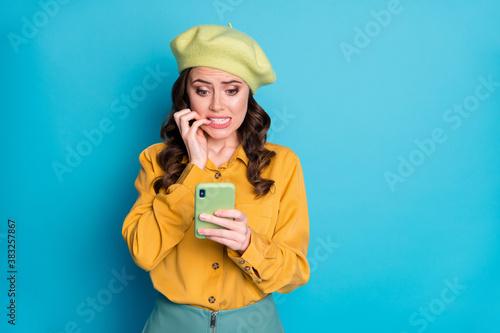Fototapeta Portrait of nervous girl use smartphone read horrible terrible blogging social network corona virus information bite finger nails wear yellow shirt headwear isolated blue color background obraz