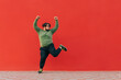canvas print picture - Portrait of funny fat dancer in casual clothes dancing on red wall background and looking aside at empty space, isolated. A man with excess weight dances funny dances.