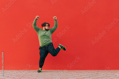 Photo Portrait of funny fat dancer in casual clothes dancing on red wall background and looking aside at empty space, isolated