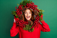 Photo Of Charming Funny Girl Hold Mistletoe Wreath Look Open Mouth Wear Red Pullover X-mas Headwear Isolated Green Color Background