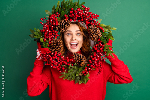 Fotografia Photo of charming funny girl hold mistletoe wreath look open mouth wear red pull