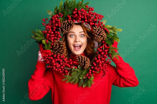 Fototapeta Photo of charming funny girl hold mistletoe wreath look open mouth wear red pull