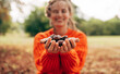 Image of smiling young woman picks chestnuts in park. Beautiful blonde female wearing an orange sweater has joyful expression resting at the autumn nature background with chestnuts in hands.