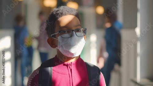 Obraz na plátně African schoolboy wearing protective mask walking in school corridor