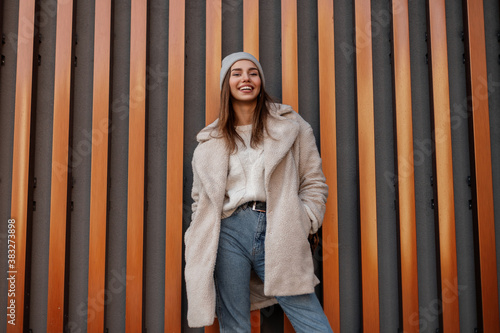 Fotografie, Obraz Joyful young woman with a cute smile in a stylish coat of milk color in blue jeans in a knit hat in a trendy sweater with a leather handbag stands and smiles near a modern building