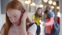 Teen Schoolgirl Being Bullied By Group Of Students In High School
