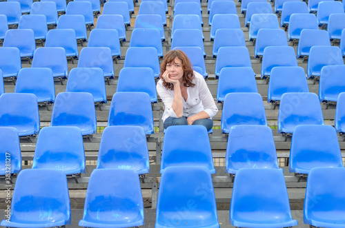 Glum woman sitting in spectator seating Fotobehang