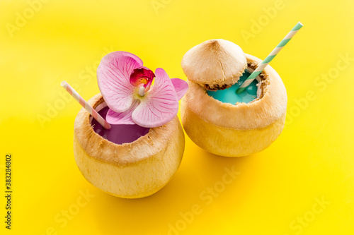 Raw coconut water or milk with straw and orchid flower, above view