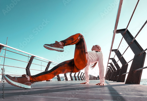Obraz outdoor workout concept. young woman in tracksuit performs sports workout on the pier - fototapety do salonu