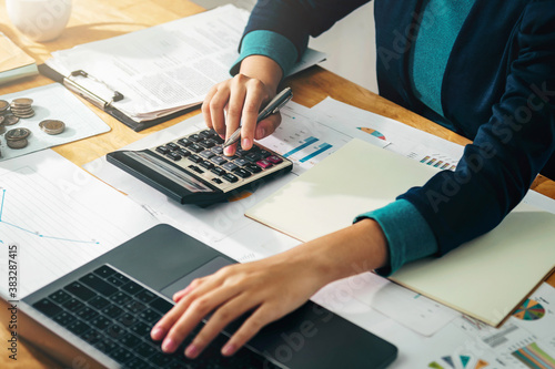 Wallpaper Mural Woman accountant use calculator and computer with holding pen on desk in office