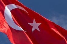 Close Up Of Waved Turkish Flag Against Blue Sky