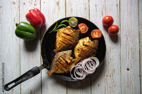 Obraz na plátně Tandoori pomfret, a popular Indian delicacy in a black pan along with condiments on a background