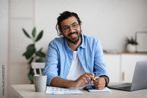Happy Indian Guy Sitting At Desk In Home Office, Smiling At Camera