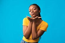Pretty Black Lady Sending Air Kiss Flirting Over Blue Background