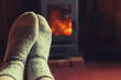 canvas print picture - Feet legs in winter clothes wool socks at fireplace background. Woman sitting at home on winter or autumn evening relaxing and warming up. Winter and cold weather concept. Hygge Christmas eve.