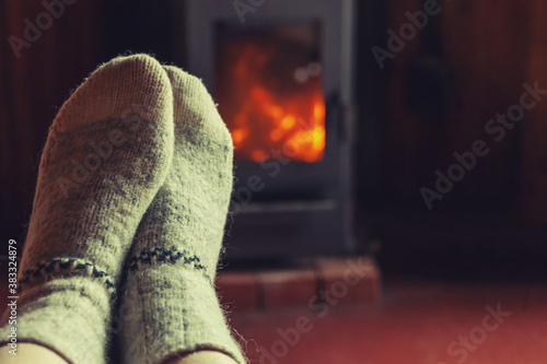 Obraz na plátně Feet legs in winter clothes wool socks at fireplace background