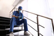 Leinwandbild Motiv Exhausted doctor sitting on stairs indoors. Stress of health care workers during COVID-19 pandemic