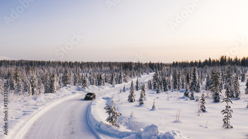 Fototapeta Bird's eye view of vehicle car moving on rural road having good insurance for winter weather, aerial view of suv automobile driving in scenery area surrounded by coniferous forest. obraz