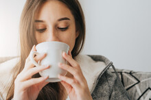 Close Up Of Young Woman Wearing Sweater Sipping Coffee Or Tea From White Mug In The Morning