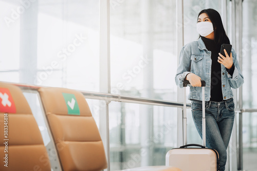 Fototapeta Happy Asian woman traveler wearing mask for protect from coronavirus holding smartphone standing with luggage next to social distancing chair obraz