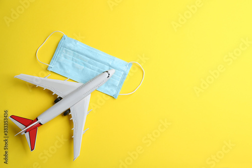 Fototapeta Toy airplane and protective mask on yellow background, flat lay with space for text. Travelling during coronavirus pandemic obraz