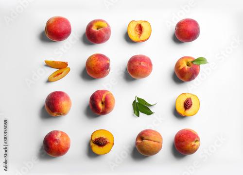Carta da parati Fresh ripe peaches and green leaves on white background, flat lay