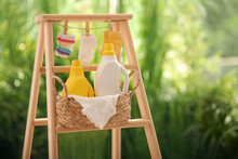 Bottles Of Detergent And Children's Clothes On Wooden Ladder Outdoors