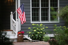 A Stereotypical American Home's Front Entrance, With The American Flag Hanging By The Front Door.