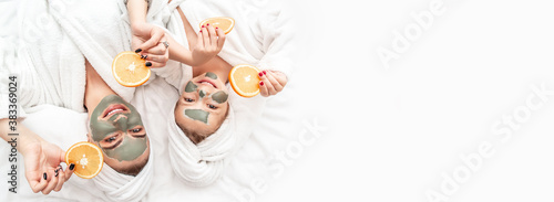 Fotografiet Happy family mother and child daughter make face skin mask with towel on head, h
