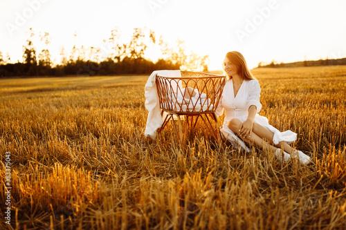 Adorable woman sitting near tiny bed with lovely newborn baby girl at the field, Canvas Print