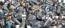 Macro Photography. Lots Of Little New Shiny Bolts. Focus In The Center Of The Photo