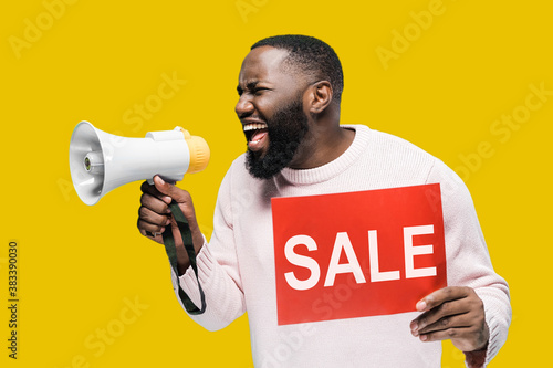 Attractive African American man emotionally shouts into a megaphone and holds a Fototapeta