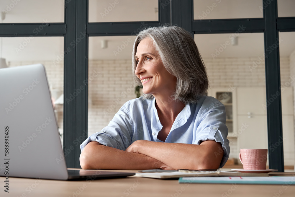 Fototapeta Smiling stylish mature middle aged woman sitting at home office workplace looking away. Happy older senior 60s businesswoman entrepreneur dreaming, relaxing, thinking of business vision concept.