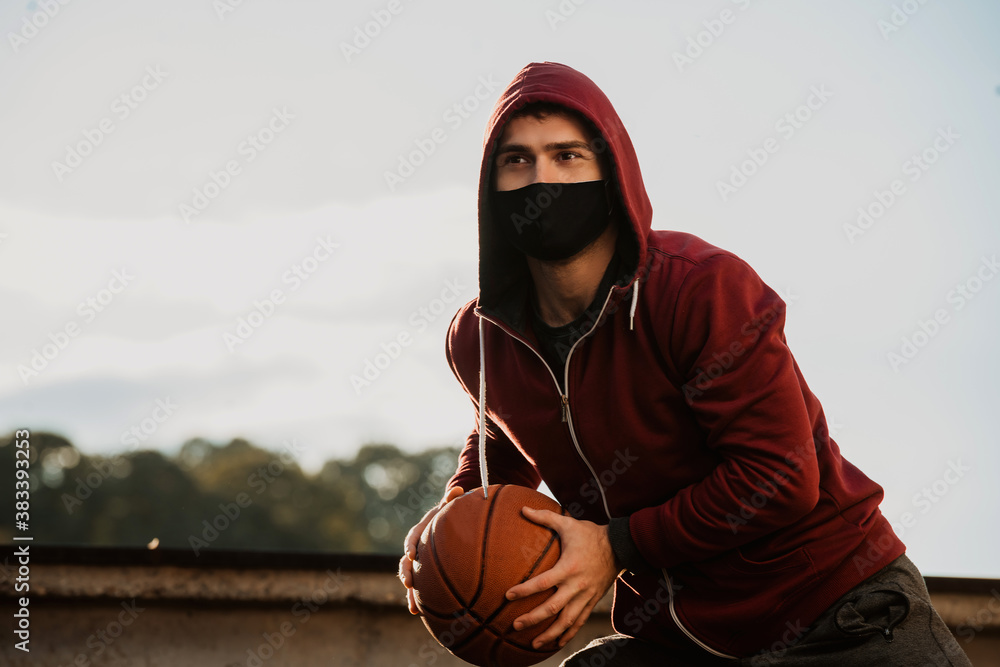 Fototapeta A young man with a face mask holding a basketball.