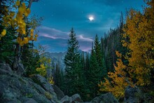 Mountain Peak In Rocky Mountain National Park Near Estes Park In Colorado. Taken In The Evening Of The Night Sky, Fall Leaves, Stars, And Moon.