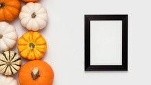 Black Frame And Pumpkins On White Background With Place For Text. Halloween Flat Lay Composition, Top View.