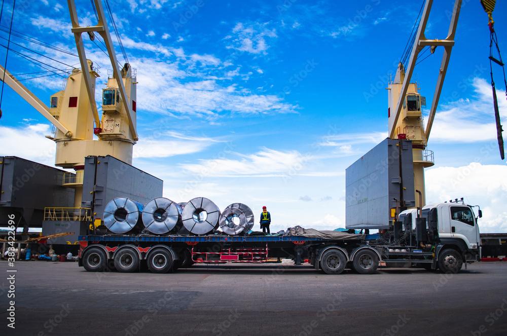 Fototapeta Truck receive steel coils alongside large cargo ship at port