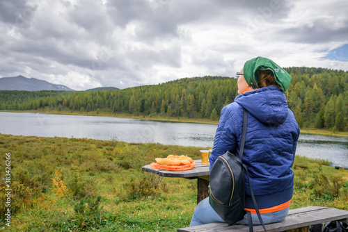 Photo Young woman traveler sitting back to the camera and admiring the beautiful view of mountains