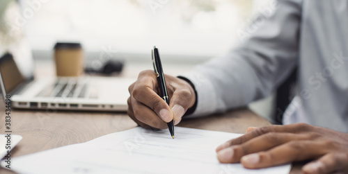 Photo Young man signing an official document, male hand holding pen putting signature at paper contract agreement