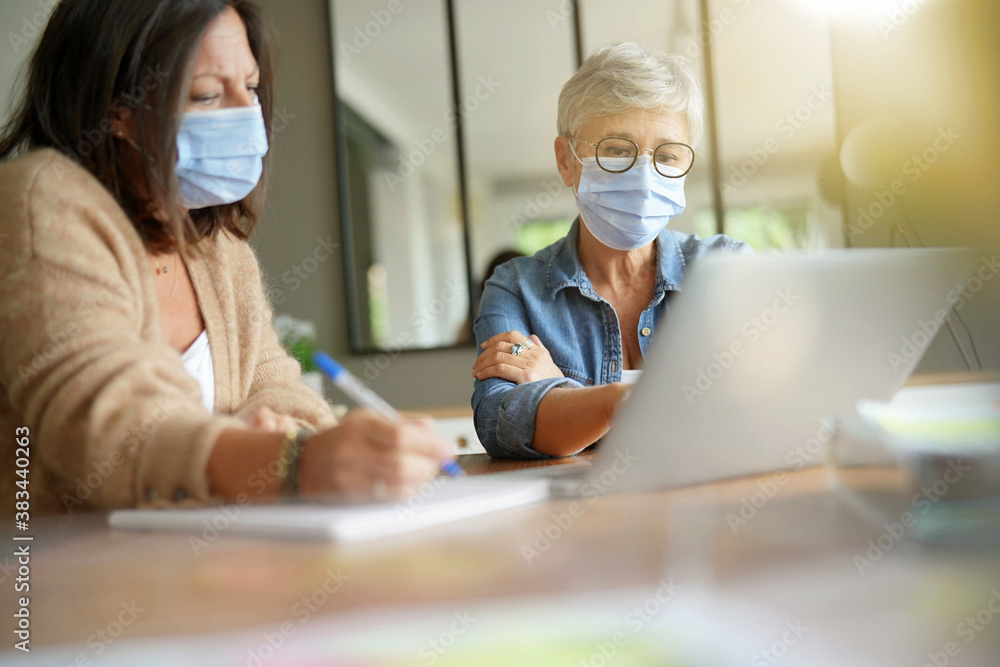 Fototapeta Business women working in office with face mask