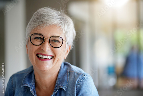 Photo portrait of a beautiful smiling 55 year old woman with white hair