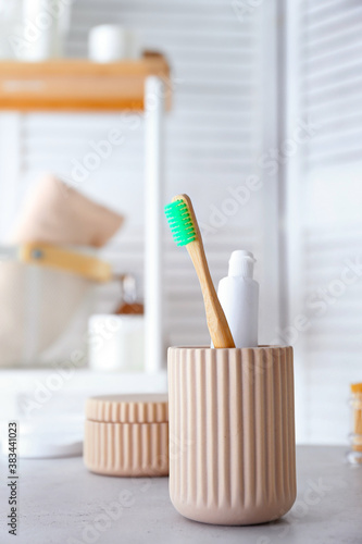 Fotografija Cup with tooth brush and paste in bathroom