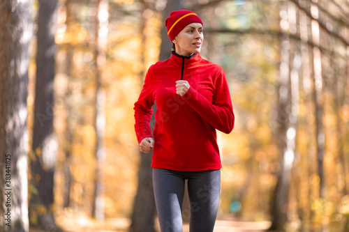 Tablou Canvas Adult caucasian slim woman in red sportswear and a cap jogging in the forest in