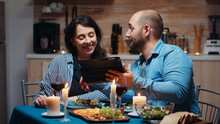 Young Caucasian Husband Using Tablet During Festive Meal Showing To His Wife Holiday Destinations. Adults Sitting At The Table, Browsing Online, Surfing, Using Smartphones, Enjoying The Meal