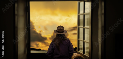 a silhouette of a girl with a hat looking at admiring outdoor sunset on the window Wallpaper Mural