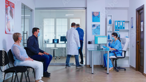 Fototapety, obrazy: Senior man filling document in hospital waiting area before medical examination. Nurse wearing face mask against infection with coronavirus. Private hospital busy waiting area